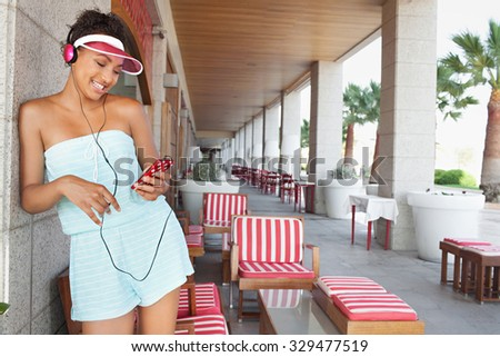 Americana black teenager girl standing at bar on a summer bright day, using a smartphone and headphones to enjoy listening to music, smiling. Fun technology and retro adolescent lifestyle, outdoors. - stock photo