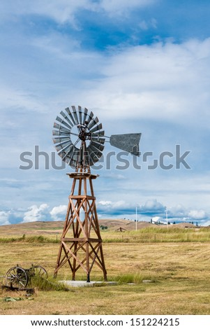 Americana Vintage Windmill on grassy field.  Blue sky with white clouds. Vertical. Copy space. - stock photo