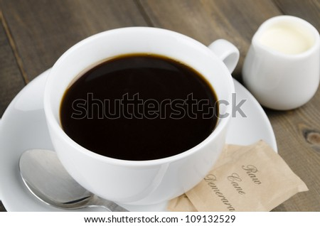 Americano black coffee in a white cup with raw demerara sugar sachets and a jug of milk. Close up. - stock photo