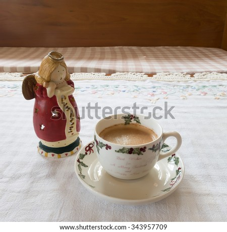 Americano coffee in christmas cup and angel candle holder on scott fabric. - stock photo