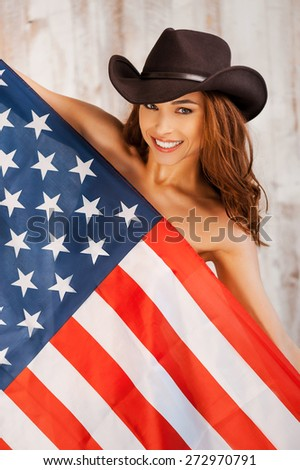 Americasn beauty. Beautiful young shirtless cowgirl wearing hat and covering herself by American flag while standing against the wooden background