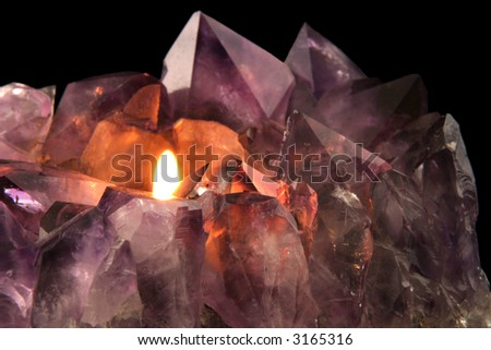 Amethyst Candlelight - Quartz crystal used in alternative medicine to alleviate stress and anxiety. - stock photo