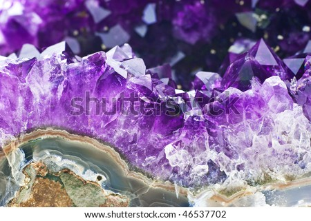 Amethyst druse over agate rock - stock photo