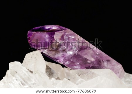 Amethyst sharp shaped crystal energizing on druze of quartz crystals (black background). Amethyst is used in alternative medicine and esoteric for work with energies and is conected with 7th chakra. - stock photo