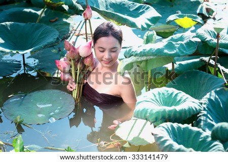 amezing of beautiful young woman Farmer  collecting lotus in garden. thai lifestyle  people in local,Thailand - stock photo