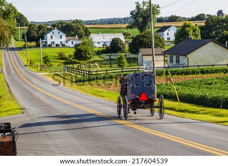 Amish buggy goes down road in rural Pennsylvania. - stock photo