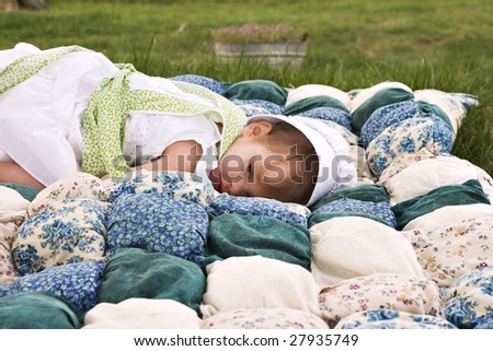 Amish child lying outdoors on a handmade biscuit quilt. - stock photo
