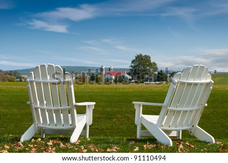 Amish Country Adirondack Chairs - farm view rest - stock photo
