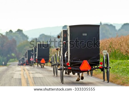 Amish horse and buggies traveling in lancaster county, pennsylvania in the fall - stock photo