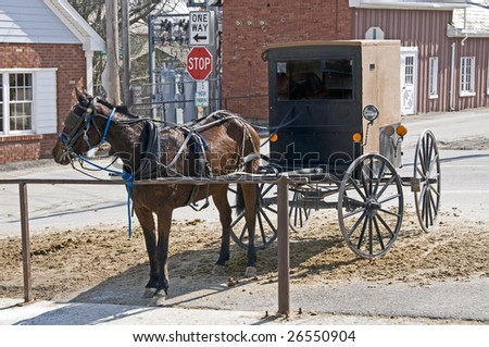 Amish horse and buggy hitched to a post in a modern community - stock photo