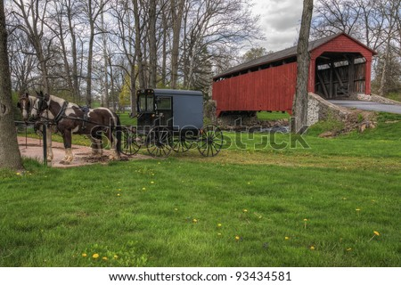 Amish horses and buggy parked near a covered bridge in Lancaster County, Pennsylvania.
