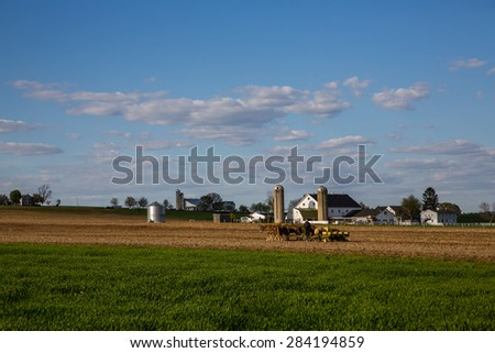 Amish man operating a horse drawn plow in the fields of rural Lancaster County Pennsylvania shot wide angle. - stock photo