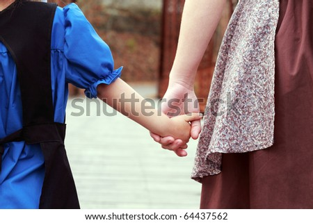 Amish or Mennonite mother and child holding hands as they walk across an old covered bridge. - stock photo