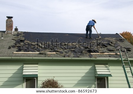 Amish workman removing old shingles to prepare a roof for a new installation - stock photo