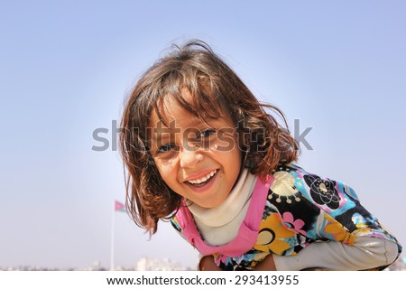 AMMAN, JORDAN - APRIL 07: unidentified happy Jordan little girl asking for being photographed and smiling to the camera on the citadel top of Amman city, Jordan on April, 17, 2014 - stock photo