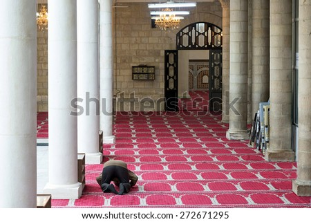 Amman, Jordan - April 03, 2015: View of a man praying in the Al Husseini Mosque. This mosque was built by the late King Abdullah in 1924 in Ottoman style. It is located in the heart of downtown Amman. - stock photo