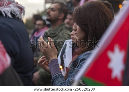 AMMAN/JORDAN - FEB 06 2015: Woman (Un-known) holds a candle in memory of the Jordanian fighter pilot Moaz al-Kasasbeh who was burnt alive by ISIS militants in Syria.