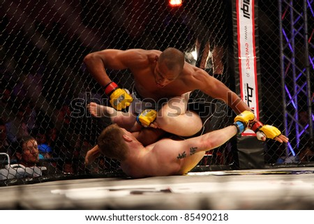 AMMAN, JORDAN - SEPTEMBER 8 : Gael Grimaud (top) vs Arni Isaksson (bottom) fight on Cage Warriors FC Vacant Welterweight Championship Title  on September 8 2011 at the new Boxing Arena in Amman, Jordan. - stock photo