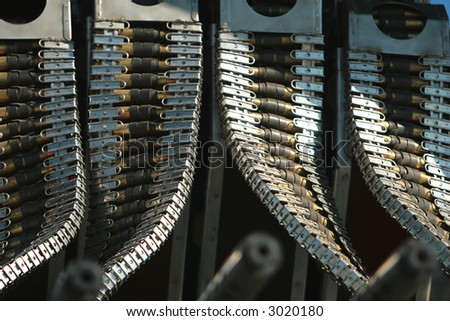Ammunition clips on a WWII B24 airplane. There are four rows and the browning machine guns can be seen in the foreground. - stock photo