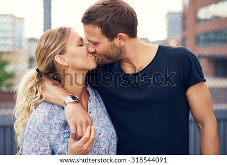 Amorous attractive young couple enjoy a romantic kiss as they stand arm in arm outdoors in an urban street - stock photo