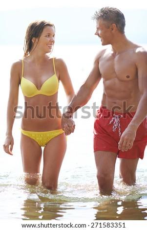 Amorous couple in swimwear walking in water - stock photo