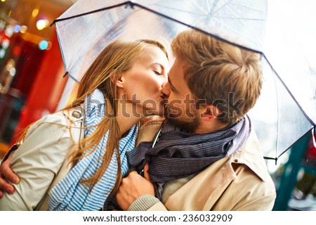 Amorous couple kissing under umbrella in urban environment - stock photo