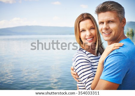 Amorous couple looking at camera during summer rest - stock photo