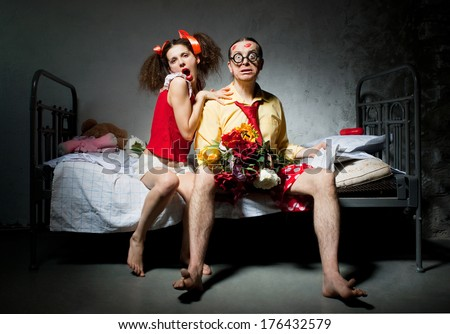 Amorous couple sitting on the bed - stock photo