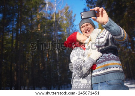 Amorous girl kissing her boyfriend while he making their selfie in natural environment - stock photo