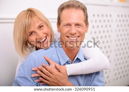 Amour in air. Vivacious pleasant smiling adult couple embracing and expressing joy while having great time together - stock photo