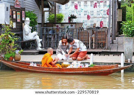 AMPHAWA, THAILAND -NOV 07 : Buddhist monks are given food offering from people for End of Buddhist Lent Day. on November 07, 2014 in  Amphawa ,Thailand. - stock photo