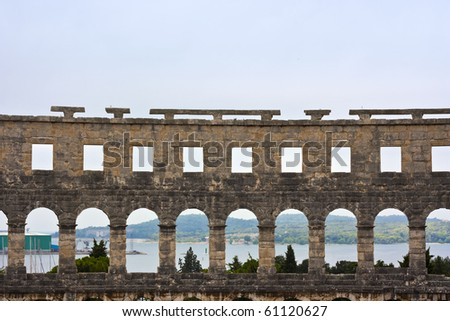 Amphitheater with harbor and trees in the background in Pula in Croatia - stock photo