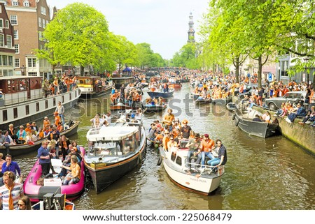 AMSTERDAM - APRIL 26: Amsterdam canals full of boats and people in orange during the celebration of kings day on April 26, 2014 in Amsterdam, The Netherlands - stock photo