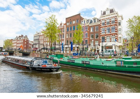 Amsterdam-April 30: Boat trip through Amsterdam canals with houseboats along the canal, people enjoy sightseeing on April 30,2015, Netherlands. - stock photo