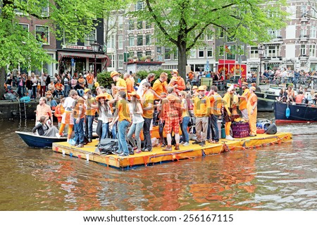 AMSTERDAM - APRIL 26: Canals of Amsterdam full of people in orange on boats during the celebration of kings day on April 26, 2014 in Amsterdam, The Netherlands - stock photo