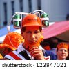 AMSTERDAM - APRIL 30: City natives and tourists celebrate Queen's Day, Dutch annual national holiday, in the streets of the city, on April 30, 2001 in Amsterdam, The Netherlands - stock photo