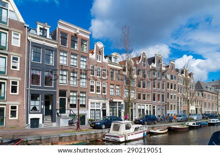 AMSTERDAM - APRIL 4, 2015: Facades of monumental houses in the city center. Amsterdam is built on approximate 11,000,000 wooden poles that sink in the mud. - stock photo