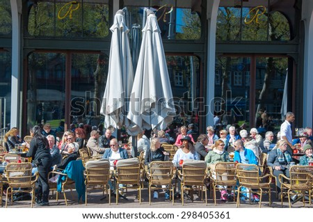 Amsterdam-April 30: Undefined people have drinks in outdoor cafe with Rembrandtplein view on April 30,2015, the Netherlands. - stock photo