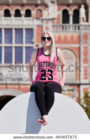 AMSTERDAM-AUG. 27, 2014. Blond girl on sculpture at Museum Square. Amsterdam is the most visited Dutch city (4.3 million foreign guests) with 1,200 bridges and 165 canals called Venice of the North.