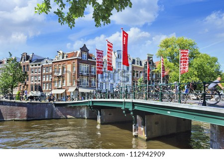 AMSTERDAM-AUG. 18: Canal and bridge on Aug. 18, 2012 in Amsterdam, The Netherlands. It is known as Venice of the North, its beautiful canal belt was finally added to the world heritage list in July 2010. - stock photo
