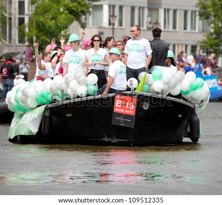 AMSTERDAM - AUG 4: City natives and guests on board of Dutch trade union federation boat participate in the Canal Parade, held on August 4, 2012, Amsterdam, The Netherlands