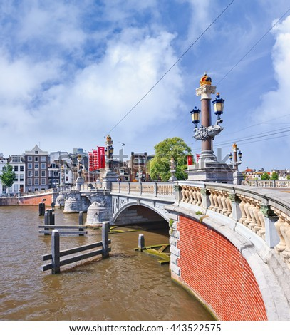 AMSTERDAM-AUG. 19, 2012. Ornate ancient bridge against a blue sky. Amsterdam is known as Venice of the North, its beautiful historical canal belt was finally added to world heritage list in July 2010.