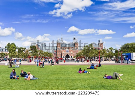 AMSTERDAM-AUG. 24, 2014. People enjoy a summer day on Museum Square. Several museums are located around the very touristy square: Rijksmuseum, Van Gogh Museum, Stedelijk Museum and Diamond Museum. - stock photo