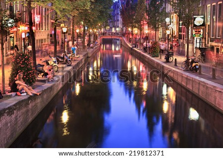 AMSTERDAM-AUG. 19, 2012. Red Light District at night. It is probably the world's most famous in its kind. There are over 500 windows in the Amsterdam Red Light District and about 1000 working girls. - stock photo