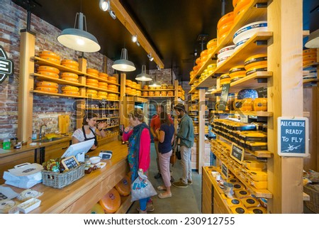 AMSTERDAM - AUGUST 29: Cheese wheels are on the shelves in the store on August 29, 2014 in Amsterdam. - stock photo
