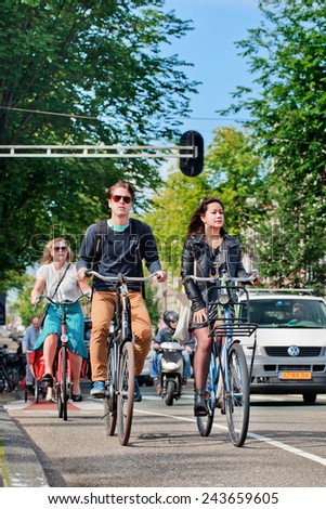 AMSTERDAM-AUGUST 27, 2014. Fashionable citizens on bicycles. In a city with 800,000 people, there are 880,000 bicycles, the municipal government estimates, which is four times the number of its cars. - stock photo