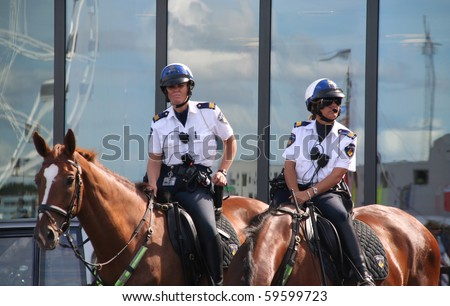AMSTERDAM- AUGUST 19 : Female police officers on horseback watch the crowd at Sail 2010 in Amsterdam, Holland on august 19, 2010 - stock photo