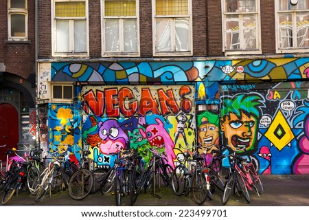 AMSTERDAM - AUGUST 29: Lots of bikes parked in front of a building painted with graffiti on August 29, 2014 in Amsterdam. - stock photo