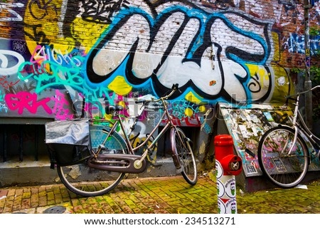 AMSTERDAM - AUGUST 31: Traditional dutch bicycle parked near brick wall painted with graffiti on August 31, 2014 in Amsterdam. - stock photo