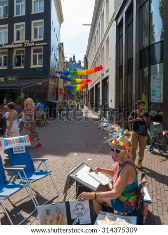 AMSTERDAM - AUGUST 2, 2015: Unknown caricaturist during the Amsterdam Gay Pride, a festive event with a gay cultural character. It is held annually since 1996 during the first weekend of August.